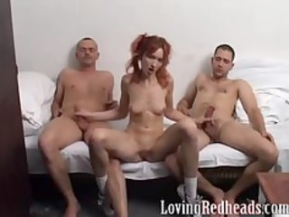redhead gives handjob to two guys